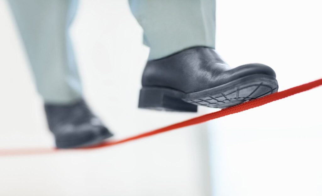 Business man walking a red tight rope
